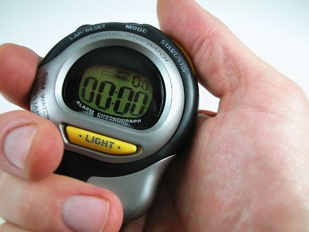 A close-up shot of a Caucasian man's hand holding a digital stop watch