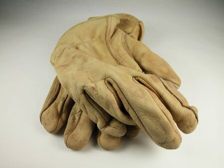 Front view of worn leather work gloves against a neutral background