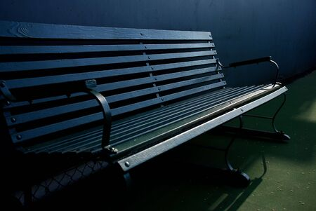 Classic dark green bench on a tennis court