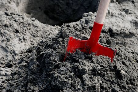 Red Shovel in Sand with Hole