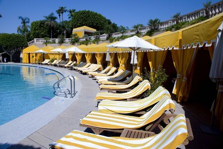 Pool Side Yellow Cabanas and Striped Towels