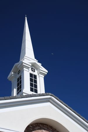 A vertical shot of a white church spire with dark windows taken against a deep blue sky. Stock fotó
