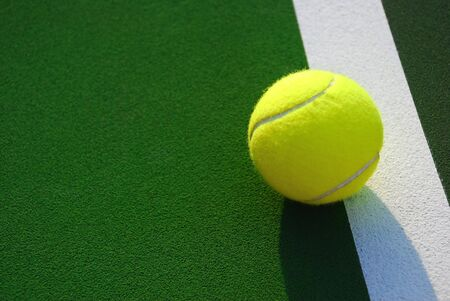 A bright yellow tennis ball sitting on the line with the green court and lots of copy space