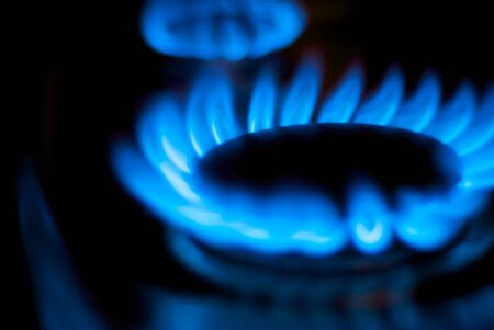 gas stove: A close up shot of blue flames from a natural gas burner in a home kitchen.