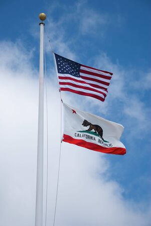 USA and California flags on white pole photo