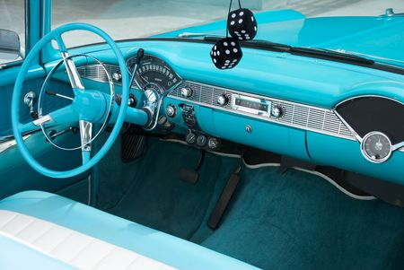 fuzzy: Interior shot of a blue colored 1956 convertible with fuzzy dice
