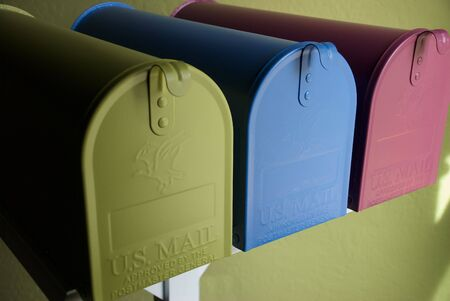 postmaster: Green Blue and Plum Colored Mailboxes in a Row Stock Photo