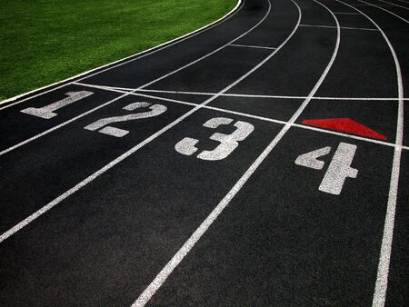 cushioned: The Black Surface of a Cushioned Running Track with Marked Lanes Stock Photo