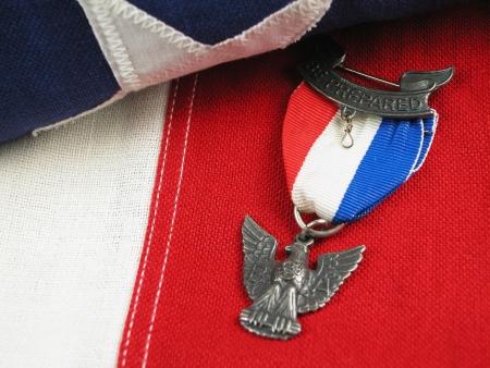 Close-up van een Eagle Scout Award zittend op een vlag Stockfoto