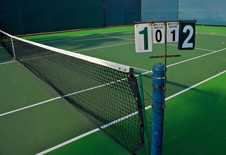 An old tennis court with net and score board
