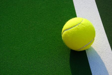 foul: Close up of a yellow tennis ball resting on the white foul line