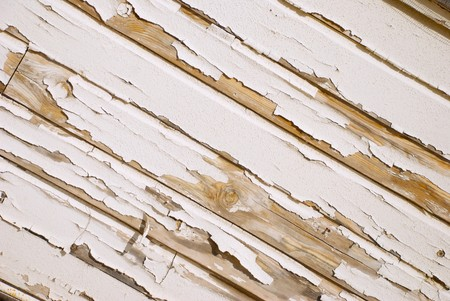 A very old wooden slat wall with serverly distressed and cracked paint photo
