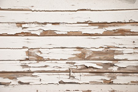 A very old wooden slat wall with serverly distressed and cracked paint