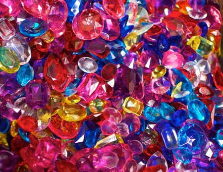 A field of brightly colored plastic jewels which are pink, red, blue and yellow in color