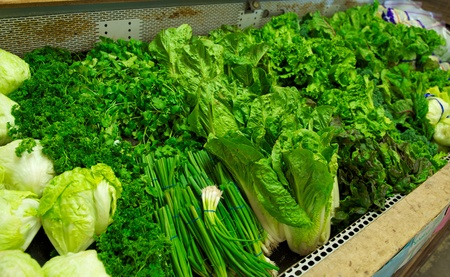 produce sections: A bright green section of produce including onions, iceburg, parsley, romaine and other lettuces in a grocery store bin