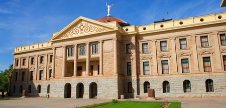An Arizona State Capital building with circular pillars topped off with a copper dome and white angel with a bright blue sky and green grass.