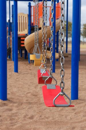 A vertical shot of school or park playground equipment with flexible swings photo
