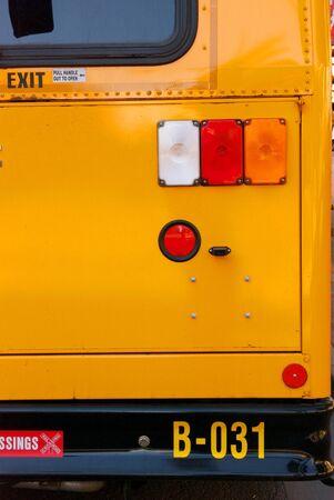 赤とオレンジの尾ライトと明るい黄色のスクールバスの黒バンパー