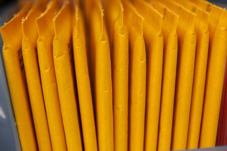 Some yellow, stuffed envelopes with cracks lined up in a row