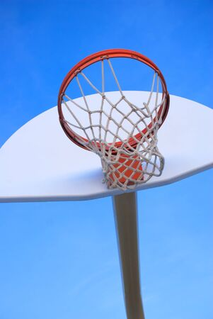 A bright orange basketball hoop on a clean white backboard shot against a clear blue sky