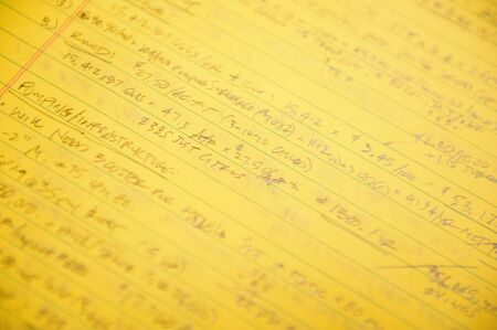 A horizontal shot of some handwritten notes and math equations on a yellow sheet of legal paper photo