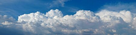 A panoramic shot of fluffy white cumulus clouds in the sky