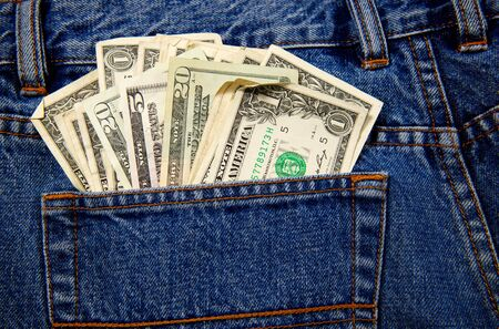 money in pocket: A back pocket of a pair of blue jeans full of currency in US Dollars