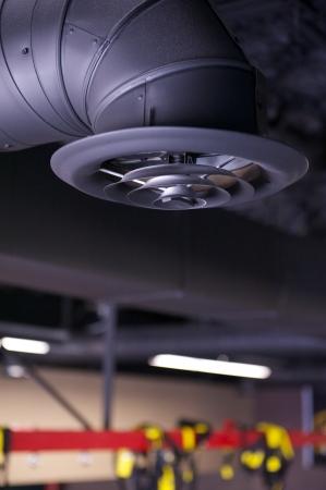 duct: Conducto Negro industrial del aire y de ventilaci�n o registro que cuelga de un techo sin terminar en un espacio comercial en construcci�n
