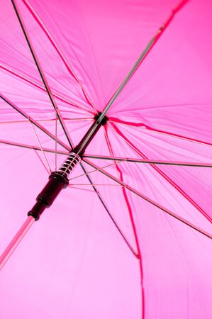 A large pink umbrella is isolated on a pure white background