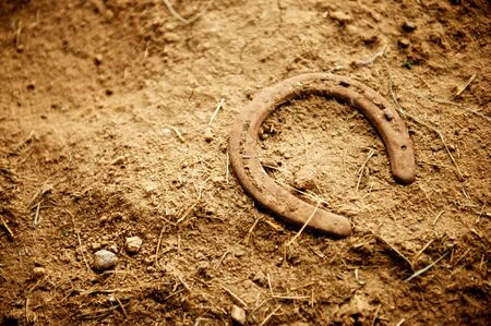 Rusty old horse shoe with a nail still in it lying alone on the dirt floor of an old barn photo