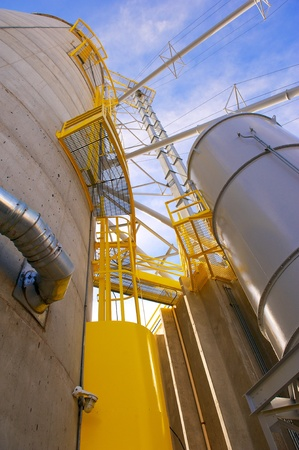food processing: Vertical shot of towering grain silos made of concrete with metal conduits and yellow access areas at a food processing plant