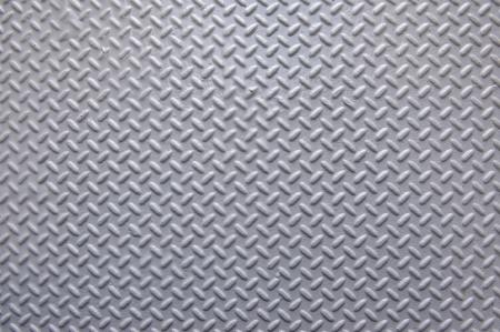 Background of painted metal with raised herringbone pattern