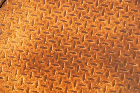 Background of a rusted manhole cover with a repetitive herringbone pattern Imagens