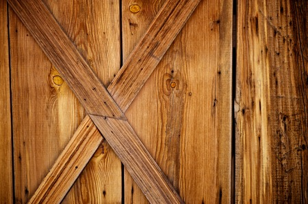 Barn door details with weathered and worn wood planks that include rusty nails and knots