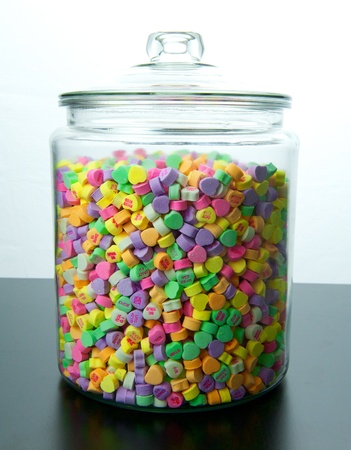 Large glass jar of colorful candy hearts with lid sits on a black table with a white background 免版税图像