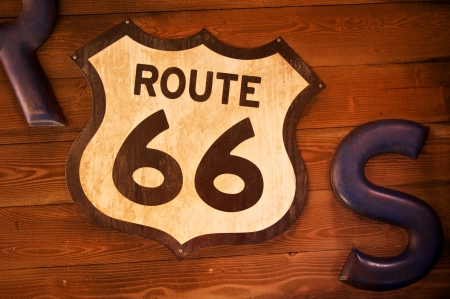 Old and rusty route 66 sign hangs on a wall made of wooden planks photo