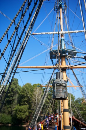 rigging: An old rusted and weathered lamp hangs from a rope on an old-fashioned sailing ship Stock Photo