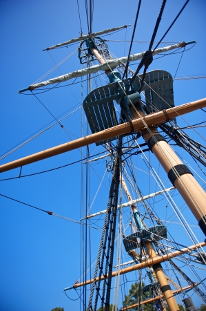 rigging: The rigging and masts of an old sailing ship against a blue sky