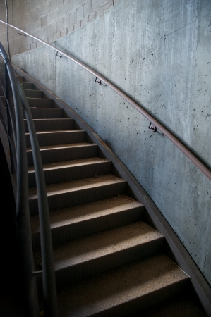 utilitarian: Curved metal staircase against a cold, gray concrete wall with handrails