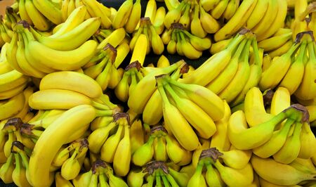 Yellow and green bananas are arranged in a pile in a grocery store