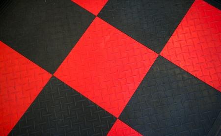 checker board: Negro y rojo antideslizante alfombra de goma con dise�o en espiga dispuesto como un tablero de ajedrez. Foto de archivo