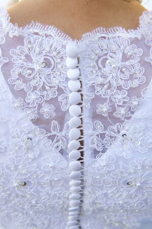 Details of a wedding gown including looped buttons, pearls and gem stones