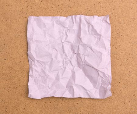 creasy: Crumpled violet note paper isolated on brown board