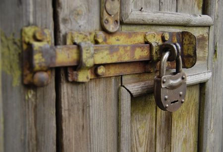 The old metal lock hanging at the door Stock Photo - 6290410