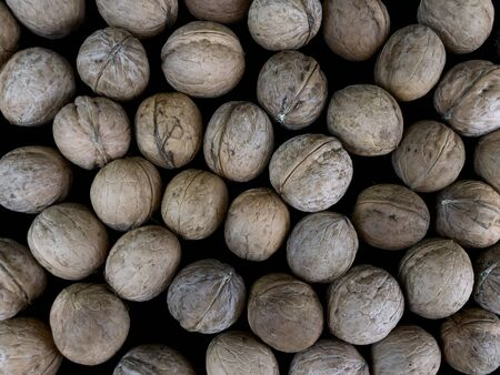 Hard walnuA pile of inshell walnuts. Freshly picked nuts lie on the ground. Autumn, nuts picking time.ts are good for your health.