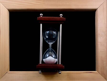 Hourglass in a wooden frame, on a black background. Glass hourglass in a frame for a picture. Glass time meter. Concept: time is running out, time is valued, time management