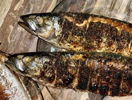 Fried mackerel cooked over a fire. Baked fish with spices lies in a plate. Close-up