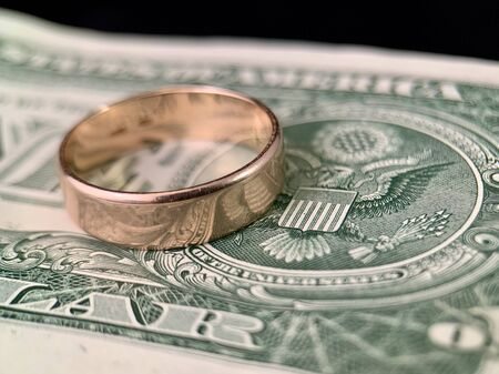 The wedding ring lies on a dollar bill. Gold ring on american dollars. Concept: marriage of convenience, engaged to money.