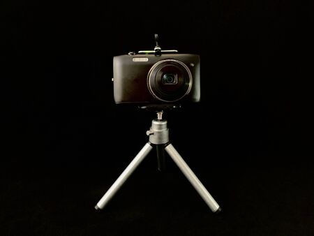 Digital camera with a small lens on a black background. Concept: home photo shooting, photo equipment Reklamní fotografie