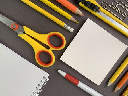 Background texture: school stationery on the desk, yellow and orange. Stationery for the office, free space for writing. Concept: back to school, scissors and paper, office supplies. Reklamní fotografie